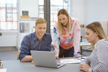junges team im büro schaut nachdenklich auf notebook