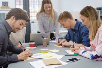 teilnehmer in einem workshop machen sich notizen