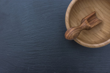 Olive wood scoop and wooden bowl on black background of slate or stone