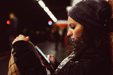Young woman using smart phone subway