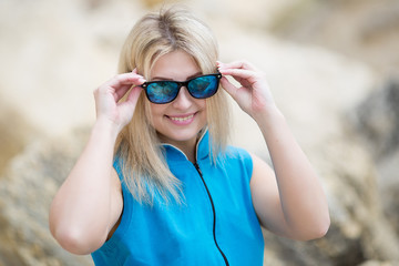 Young woman looks through tinted sunglasses at camera