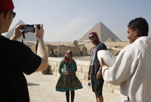 Jordan Cameron of Miami Dolphins takes a photo with a street vendor girl in front of the Sphinx at the Giza Pyramids in Giza