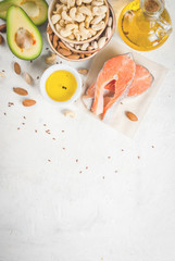 Healthy food. Products with healthy fats. Omega 3, omega 6. Ingredients and products: trout (salmon), flaxseed oil, avocado, almonds, cashews, pistachios. On a white stone table. Copy space top view