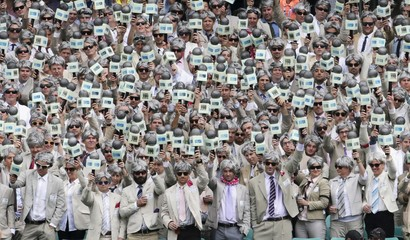 Fans dressed as late cricket player and commentator Richie Benaud wear suits, grey wigs and prop microphones, as they pay tribute to him while watching the third cricket test between Australia and the West Indies at the SCG in Sydney