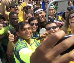 Isaquias Queiroz Dos Santos (BRA) of Brazil takes a selfie with fans after winning silver