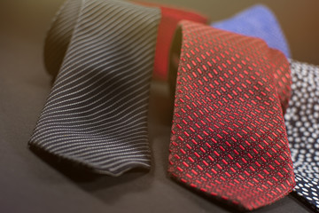 Close up of men's neckties. Modern ties for men isolated on a black background. Lens flare in the background.