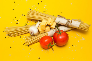 Italian pasta ingredients on a yellow background, top view