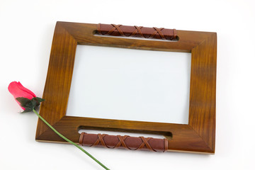 Wooden picture frame with rose flower isolated on white background. Close up  of photo frame with flower.