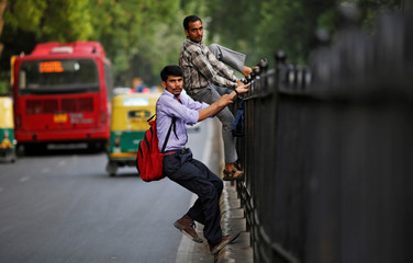 Commuters climb a fence on a road divider to cross a busy road in New Delhi
