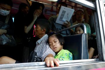 A girl sleeps while riding a public bus in Bangkok
