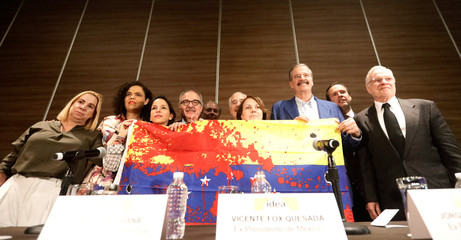 Former presidents of Latin America pose with activists while holding a flag of Venezuela after a news conference in Mexico City