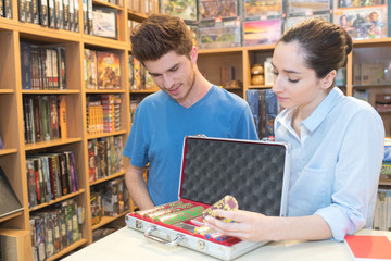 young beautiful woman shows poker chips in case to customer