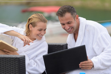 happy couple with computer at swimming pool lounge on terrace
