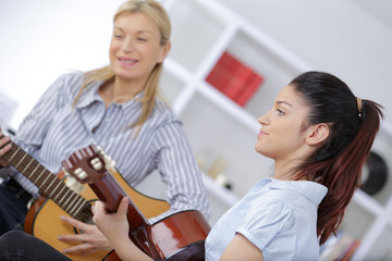 mother and daughter playing guitar together