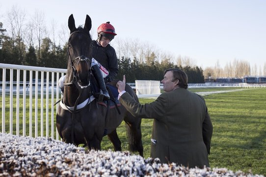 Trainer Nicky Henderson gives jockey Barry Geraghty last minute instructions before Sprinter Sacre set off for a schooling session at Newbury Racecourse. The horse who has not seen on a racecourse since being pulled up with an irregular heartbeat in the Desert Orchid Chase at Kempton last Christmas