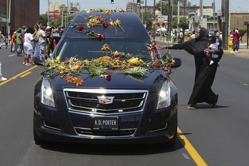 A woman runs with her child to touch the hearse carrying the body of Muhammad Ali with flowers as it drives down Broadway toward Cave Hill Cemetery in Louisville