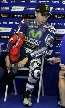 Lorenzo puts on his boots before the first qualifying session ahead of the Valencia Motorcycle Grand Prix at the Ricardo Tormo racetrack in Cheste, near Valencia