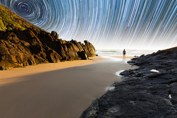 A man standing on a beautiful, isolated beach in Australia underneath a mesmerizing star trail.