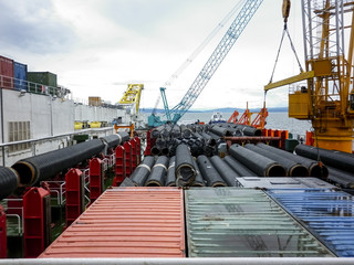 The deck lay barge. Pipes and Lifting cranes on the ship. Equipment for laying a pipeline on the seabed