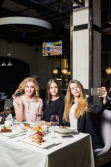 people, holidays, celebration and lifestyle concept - happy women with smartphone taking selfie at restaurant