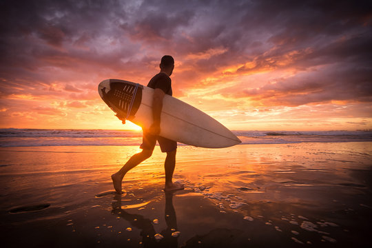 Surfer running on the beach ar sunset or sunrise