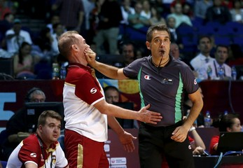 Referee Garcia covers the mouth of Venezuela's coach Garcia while he was shouting during their 2015 FIBA Americas Championship semi-final basketball game against Canada in Mexico City