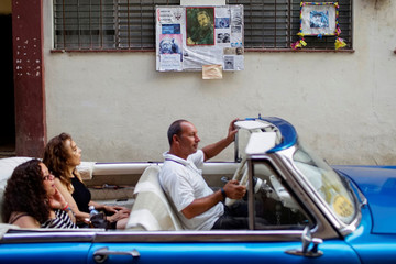 Pictures of Cuba's late President Fidel Castro hang on a wall as tourists ride in a vintage car in downtown Havana, Cuba