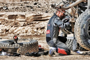 Loeb of France works on his car after he had an accident which turned the car over during the eighth stage in the Dakar Rally 2016 near Belen