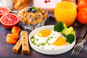 Breakfast - fried eggs with broccoli, muesli, croissant and juice on a table. Selective focus. Copy space