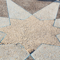 in the sidewalk star made of stone
