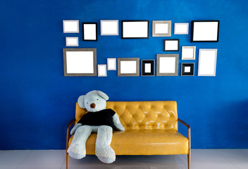 Modern living room interior ,Picture frames on blue wall and bear on yellow sofa