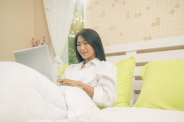 Happy casual beautiful asian woman working on a laptop sitting on the bed in the house.
