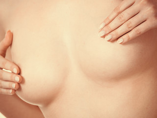 Woman examining her breasts for breast cancer