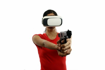 Young attractive woman in red shirt wearing virtual reality goggles holding gun