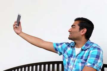 Young handsome man with arm stretched out taking a picture
