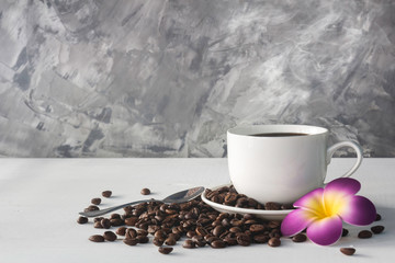 cup of coffee ,  flower and coffee bean on white wooden background with loft wall style   in concept relax time