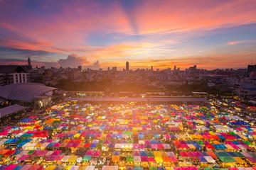 Beautiful sunset sky over night flea market with city downtown background, Bangkok Thailand