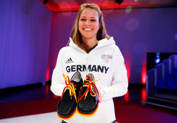 German paralympic cycling athlete Schindler holds a pair of the country's official Olympic shoes during the presentation of official uniforms for the 2016 Rio Olympics in Duesseldorf