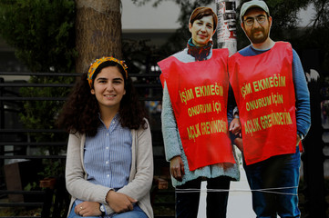 Wife of the hunger-striking teacher Ozakca, poses with pictures of her husband and professor Gulmen during a protest in Ankara