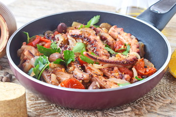 Octopus cooked in olive oil with olives, oregano, tomatoes, capers, lemon in a frying pan. Healthy eating. Mediterranean lifestyle