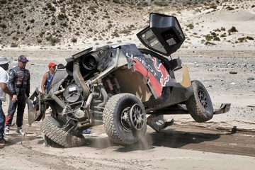 Loeb of France watches as his car falls back after he had an accident which turned it over during the eighth stage of the Dakar Rally 2016 near Belen