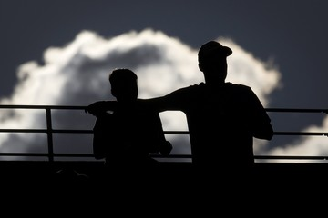 A couple are silhouetted against a cloud during the men's singles semi-final match between Federer of Switzerland and his compatriot Wawrinka at the U.S. Open Championships tennis tournament in New York