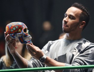Mercedes Formula One driver Lewis Hamilton of Britain looks at a traditional Day of the Dead Mexican skull adorned with Mexican crafts at the Coliseo Arena during a promotional event in Mexico City