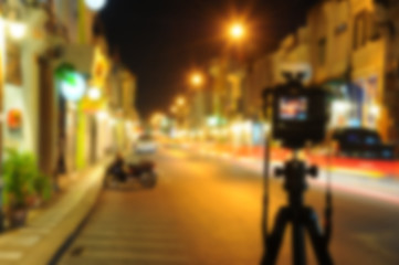 blurred camera on tripod in night street of city background