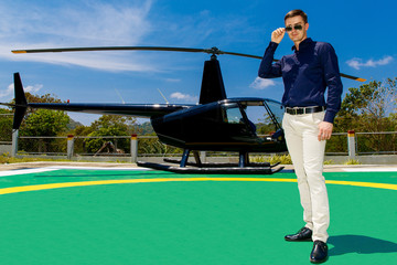 Young elegant man wearing sunglasses standing next to a private helicopter.