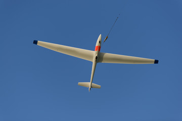 Sailplane pulled up in the sky on a line from a skylauncher