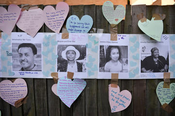 Home made posters appealing for information on people missing since the Grenfell apartment tower block caught fire are seen next to messages of sympathy in North Kensington, London
