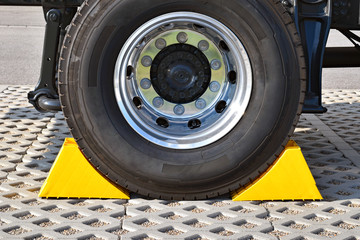 Yellow chocks at the wheel of a parked truck