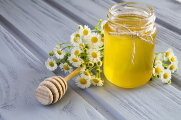 Honey and chamomiles on the grey wooden background