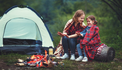 Family mother and child daughter warm their hands by bonfire on camping trip with tent